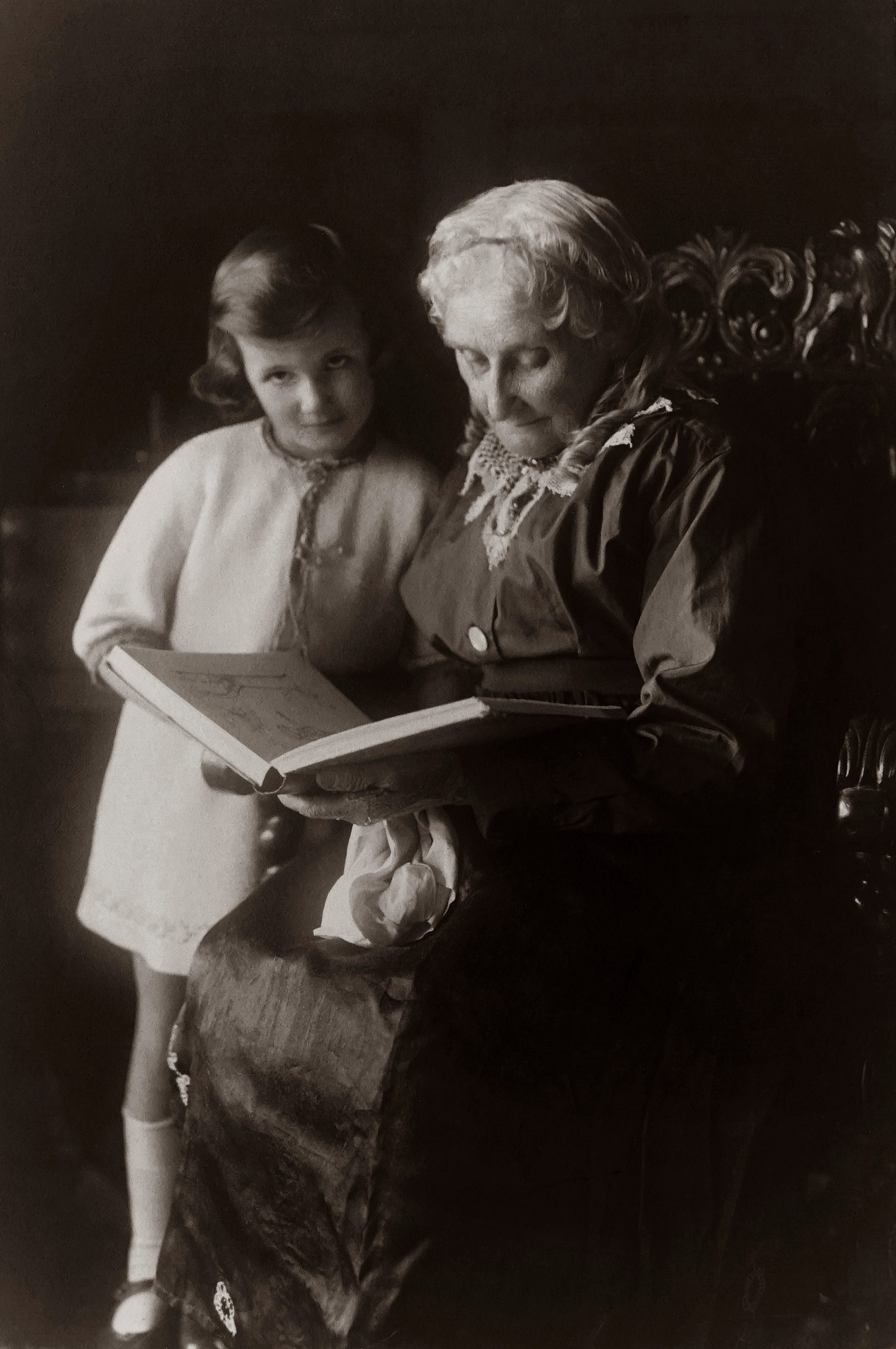 old-woman-sitting-on-chair-near-girl-while-reading-a-book-3087878